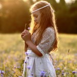 Little girl praying in field